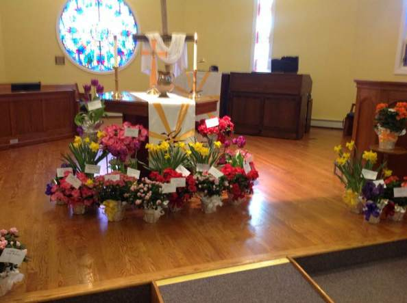 An altar surrounded with bouguets of flowers.