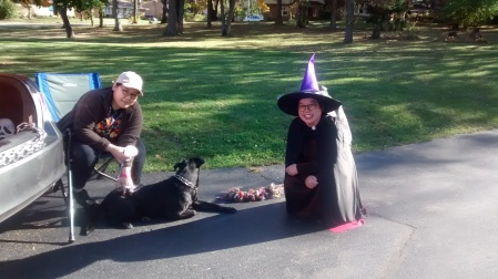 A pastor dressed up as a witch crouching next to a seated person and dog.